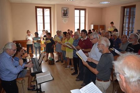 Les choristes en répétition, avec leur Chef de choeur et leur accompagnatrice.
